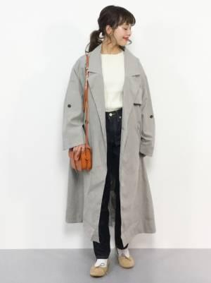 白いトップスにデニムを合わせてグレーのコートを羽織った女性