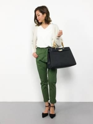 白いトップスにカーキのパンツを合わせて黒いバッグを持った女性