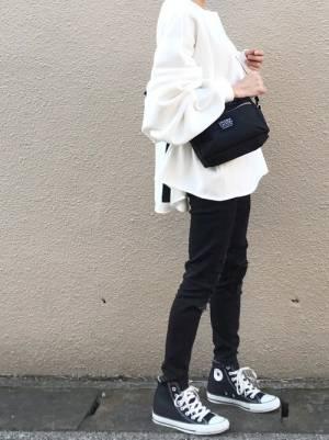 白いトップスに黒いパンツを合わせて黒いバッグを持った女性