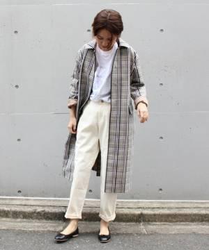 チェックのステンカラーコートに白いパンツを合わせた女性