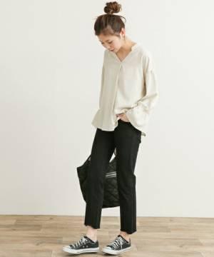 白いブラウスに黒いパンツを合わせて黒いスニーカーを履いた女性