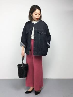 ビッグなデニムジャケットにピンクのニットパンツ、黒のかごバッグを合わせたコーデ