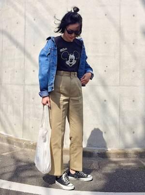 ミッキーTシャツにベージュのタックパンツを合わせ、デニムジャケットを羽織った女性