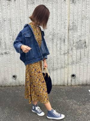 イエローの花柄ワンピースにデニムジャケットを羽織り、ブルーのスニーカーを合わせたコーデ