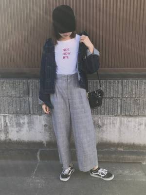Tシャツにチェックのタックワイドパンツ、デニムジャケットを羽織り、黒キャップを被った女性