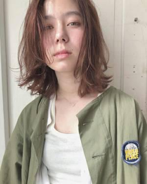 前髪をセンター分けにセットした伸ばしかけボブヘアの髪型の女性