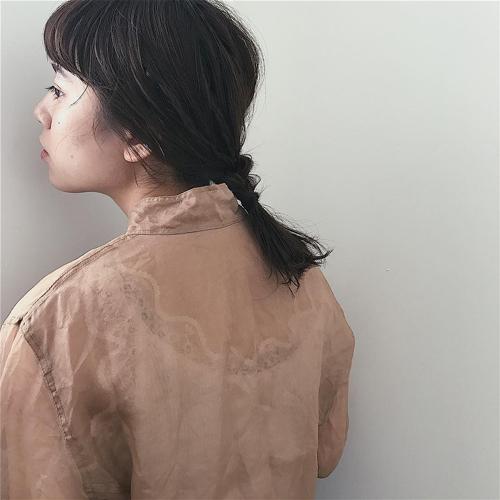 伸ばしかけのミディアムヘアを低めポニーテールにヘアアレンジした女性