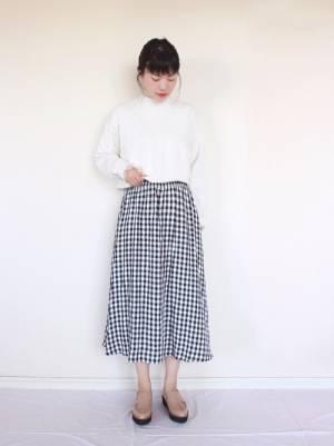 白のスウェットトップスにギンガムチェックのスカートを合わせる女性