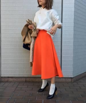 白のスウェットトップスにオレンジのスカートを合わせる女性
