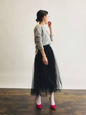 グレーのスウェットトップスに黒のチュールスカートを合わせる女性