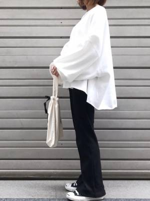 白の変形スウェットトップスに黒のパンツを合わせる女性