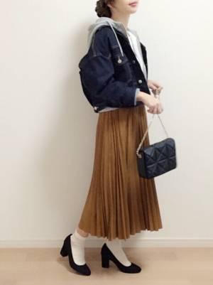 Gジャンにブラウンのスカートを合わせて黒いパンプスを履いた女性