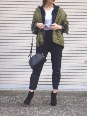 Gジャンにミリタリージャケットを合わせて黒いバッグを持った女性