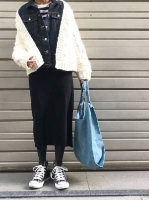 Gジャンにニットカーデを合わせてスカートを履いた女性