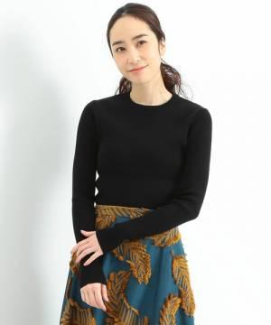 黒のリブニットにジャガードスカートを合わせて着た女性
