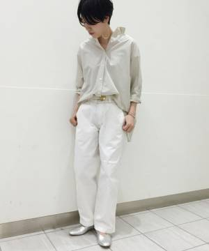 グレーシャツに白パンツを履いた女性