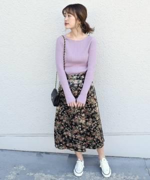紫のリブニットに花柄スカートを履いた女性