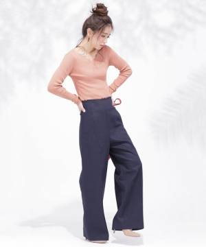 ピンクのリブニットにパンツを履いた女性