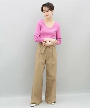 ピンクのリブトップスにベージュのチノパンを履いた女性