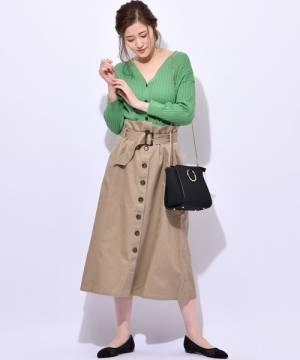 グリーンのリブカーディガンにベージュのトレンチスカートを履いた女性