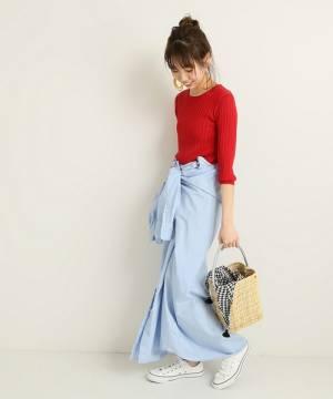 赤のリブニットにブルーのシャツスカートを着た女性