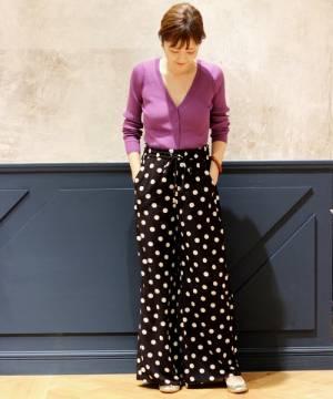 パープルのリブカーディガンにドット柄パンツを履いた女性