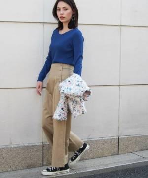 ブルーのリブニットにベージュのチノパンを履いた女性