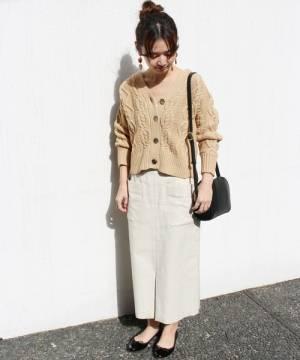 白スカートにベージュカーデを着た女性