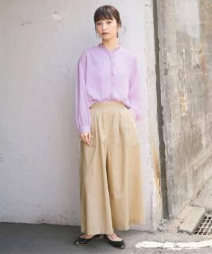 ピンクのブラウスにベージュのワイドパンツを履いた女性