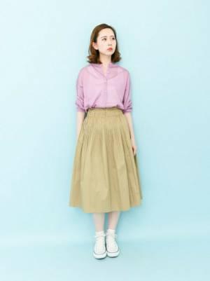 ピンクのシャツにベージュのスカートを履いた女性