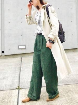 白の刺繍ブラウス、グリーンのワイドパンツにベージュのトレンチコートを着た女性
