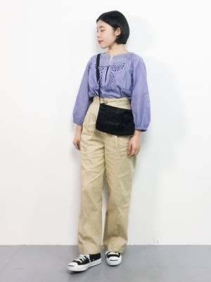 紫のブラウスにベージュのチノパンを履いた女性
