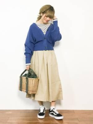ボーダートップス、ベージュのスカートにブルーのカーディガンを着た女性
