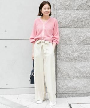 ピンクのカーディガンにベージュのワイドパンツを履いた女性