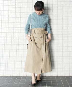 水色のリブニットにベージュのトレンチスカートを履いた女性