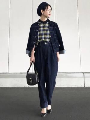 チェックのシャツに濃色のデニムジャケットとデニムを合わせた女性