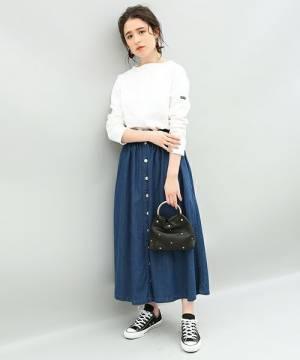 白のスウェットにフロントボタンのデニムフレアスカートを合わせた女性
