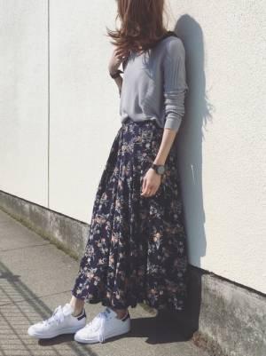 グレーのニットにネイビーの花柄のフレアスカートを合わせた女性