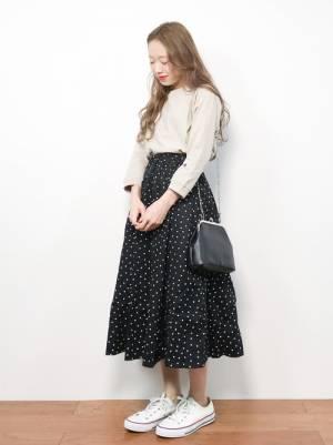 ベージュのTシャツに黒のドット柄のフレアスカートを合わせた女性