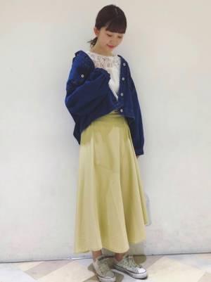 白のレーストップスにデニムジャケットを羽織り、イエローのフレアスカートを合わせた女性