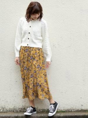白のショート丈カーディガンにイエローの花柄のフレアスカートを合わせた女性