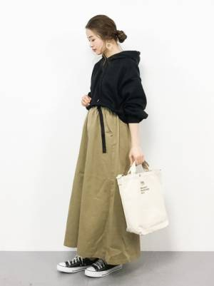 黒のパーカーにベージュのチノフレアスカートを合わせた女性