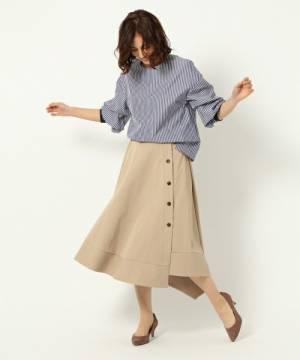 ブルーのストライプブラウスにベージュのフロントボタンデザインのイレヘムフレアスカートを合わせた女性