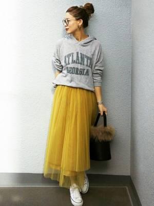 グレーのロゴパーカーにイエローのチュールスカートを履いた女性