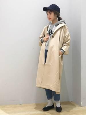 グレーのパーカー、デニムパンツにベージュのトレンチコートを着た女性