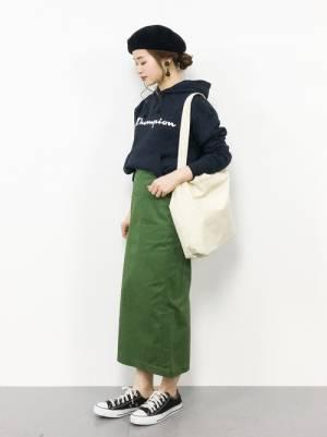 ネイビーのロゴパーカーにグリーンのタイトスカートを履いた女性