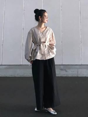 ストライプのリボンブラウスに黒のワイドパンツを履いた女性