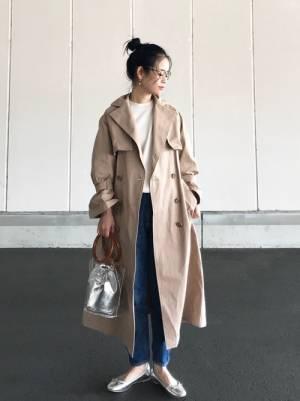白のトップス、デニムパンツにベージュのトレンチコートを着た女性