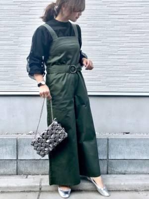 黒のチュールセーターにグリーンのサロペットを着た女性