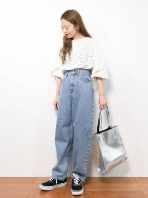 白ブラウスとデニムパンツにシルバーバッグを持った女性